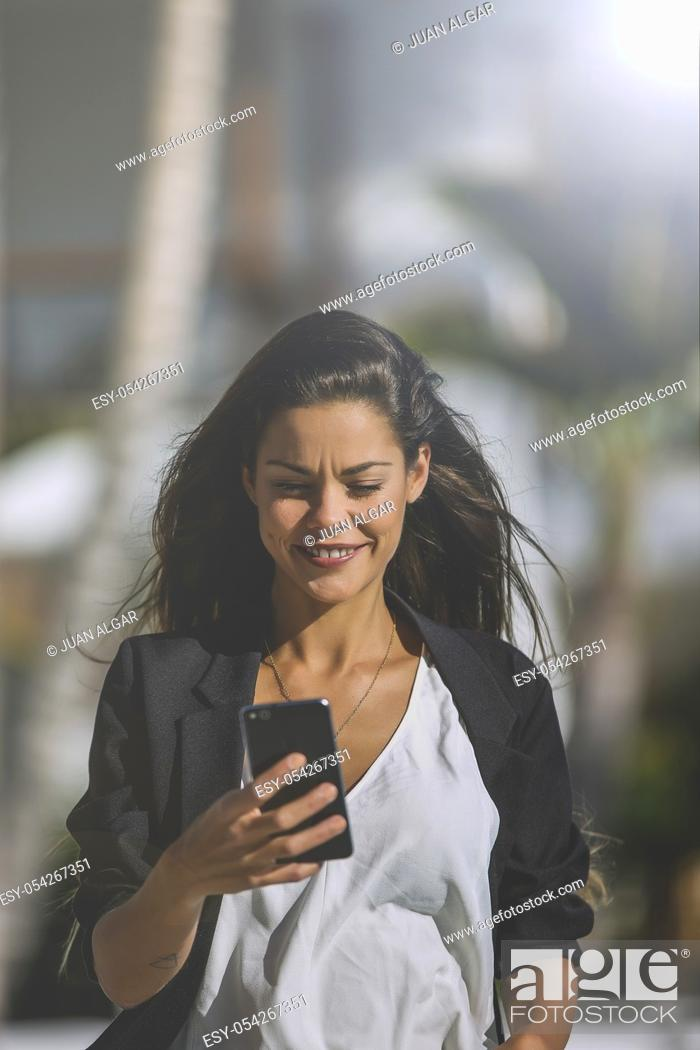 Stock Photo: Trendy brunette in black jacket surfing smartphone on territory of tropical resort walking in sunlight.