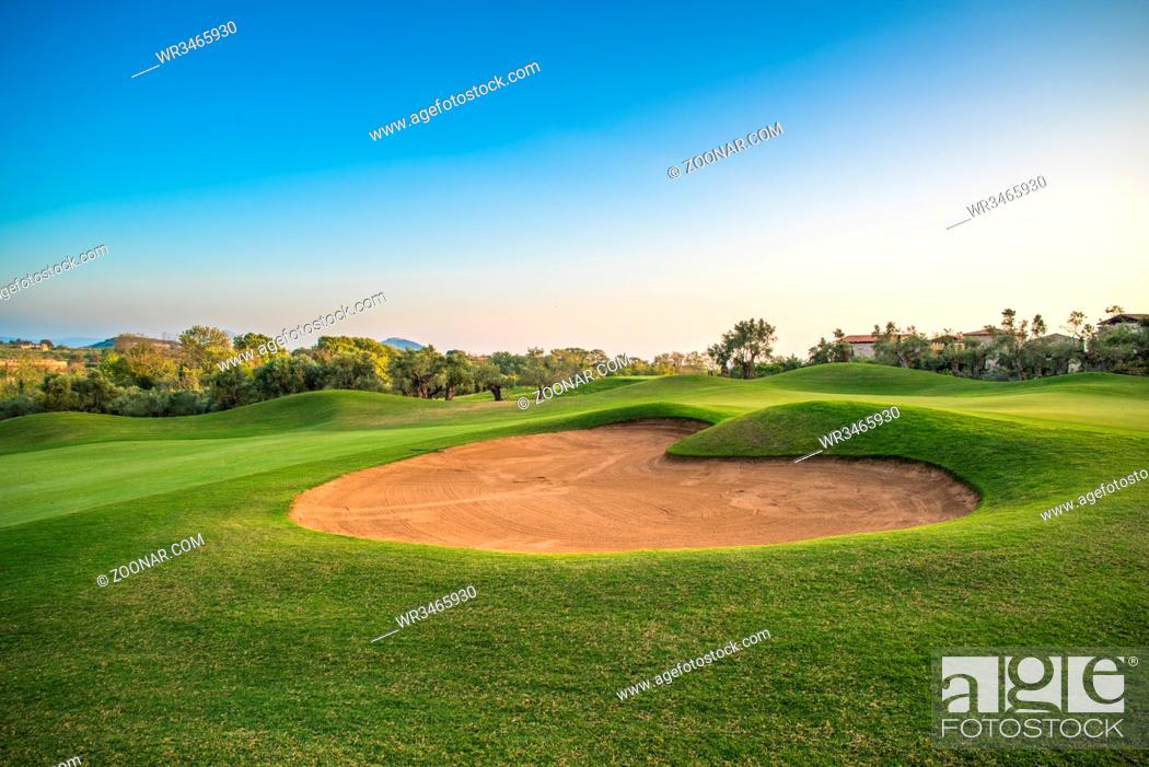 Stock Photo: Heart shape sand bunker on the green golf course.