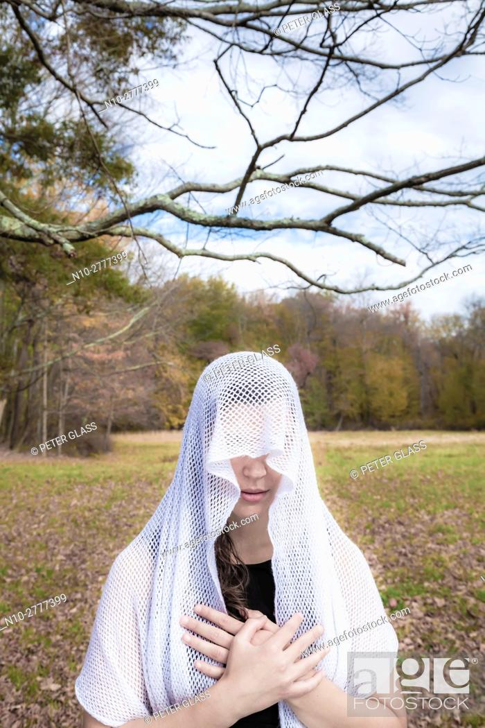 Stock Photo: Young woman, standing in an open field, wearing a veil over her head.