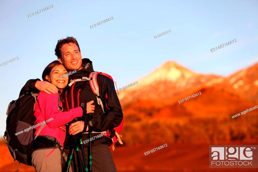 Imagen: Happy couple hiking enjoying looking at view embracing in love. Hiker man and woman wearing backpacks enjoying sunset during hike on mountain volcano Teide.