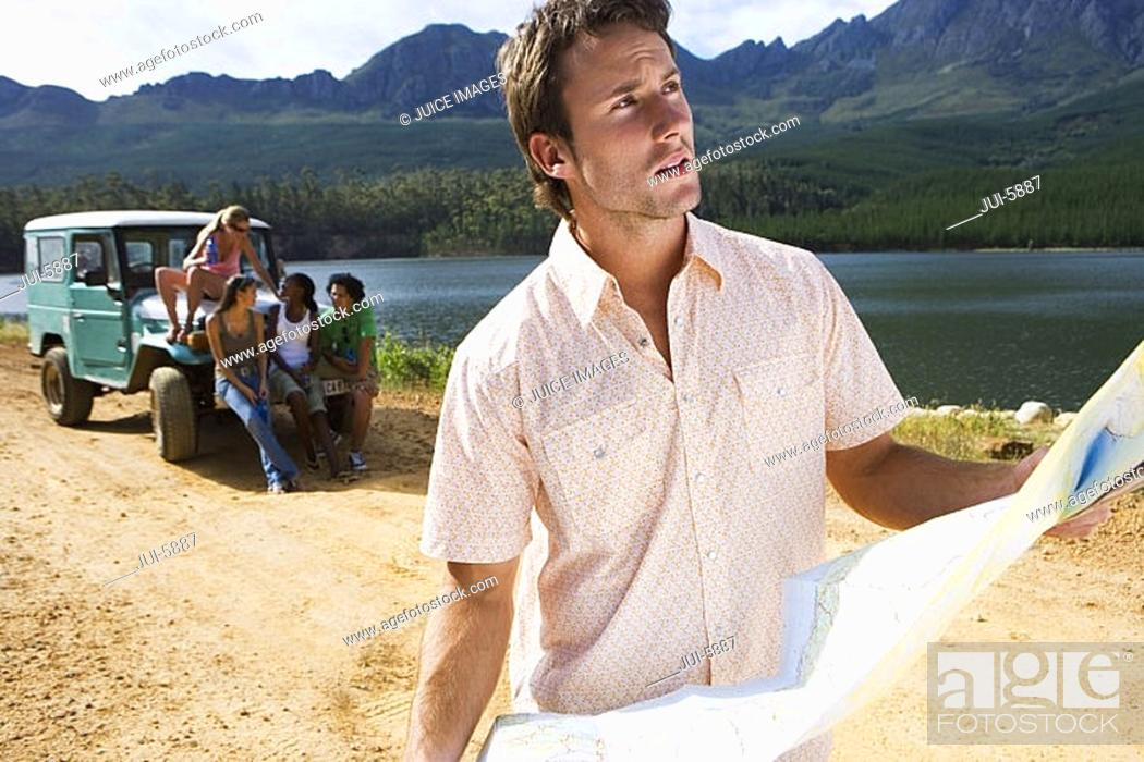 Stock Photo: Four young adults waiting by parked jeep on dirt track beside lake, focus on man consulting map in foreground.