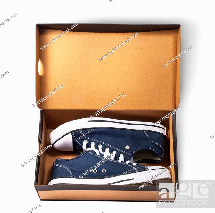 Stock Photo: Dark blue sports shoes inside cardboard box isolated on white background.