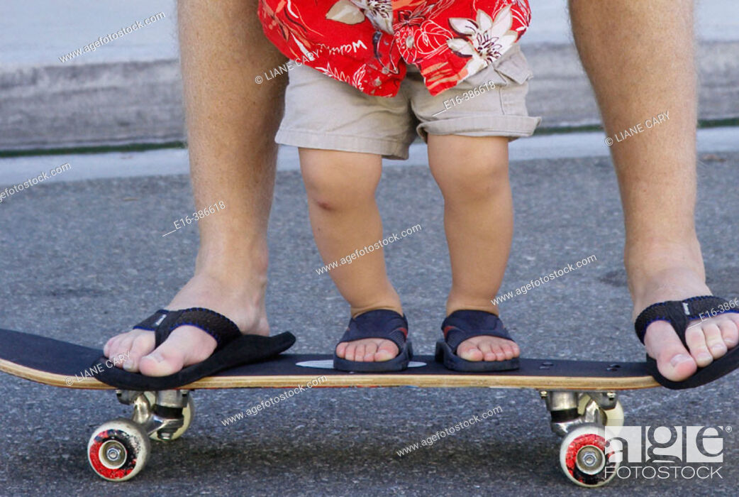 Stock Photo: father and son together on skateboard.