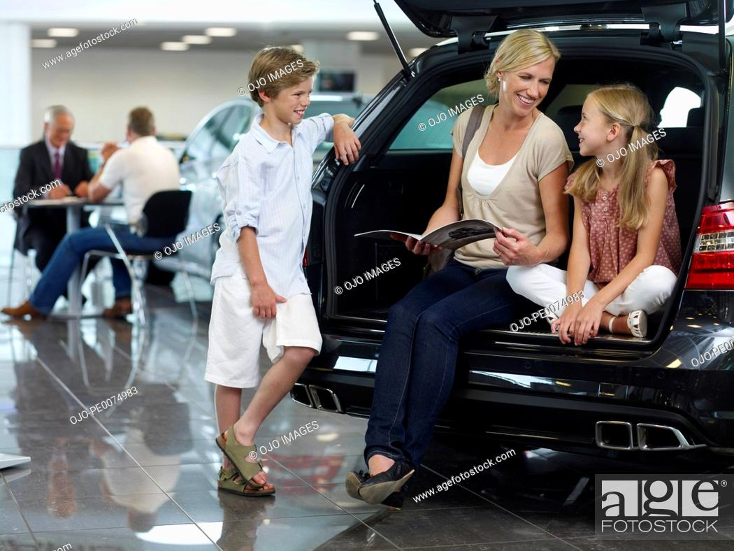 Stock Photo: Mother and children sitting in back of new car in showroom.