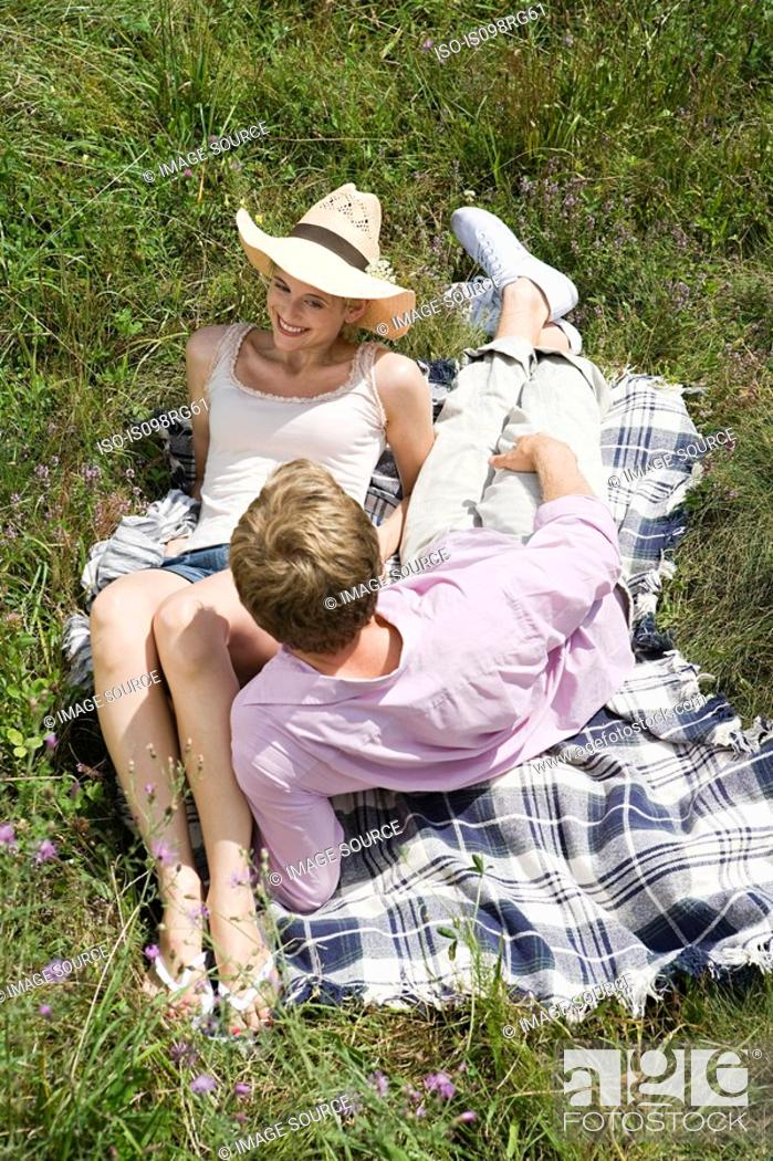 Stock Photo: Couple on a blanket in a field.