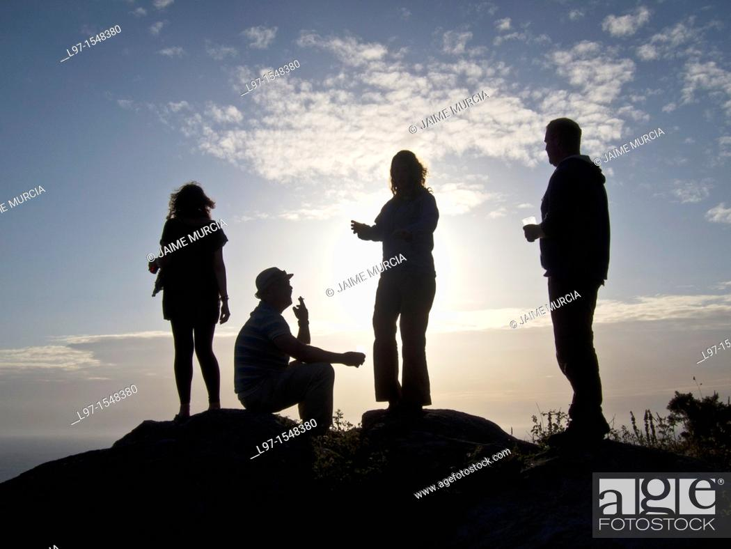 Stock Photo: Silhouette of four people at sunset village of finisterre.