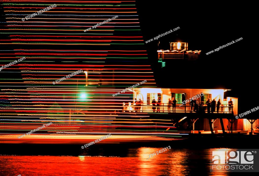Stock Photo: Christmas in St. MIchaels: Parade of lighted boats pass the Hooper Strait Lighthouse in St. Michaels Harbor.
