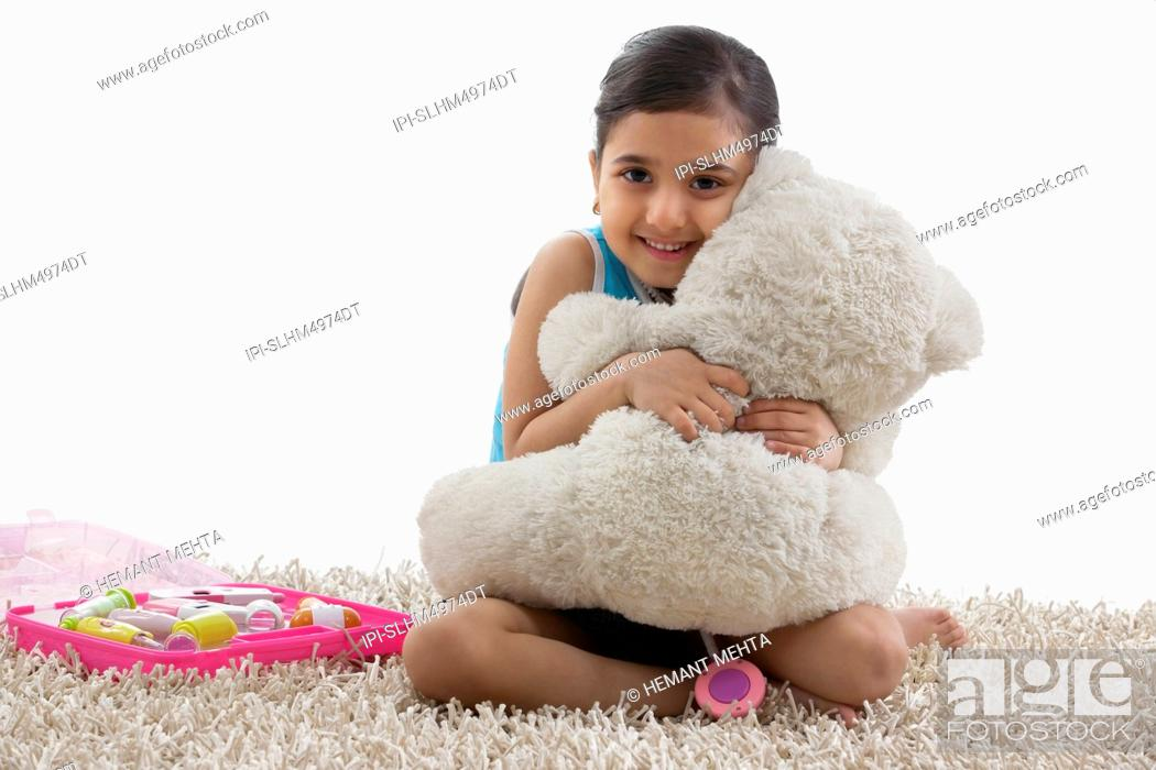 Stock Photo: Girl hugging her teddy bear.