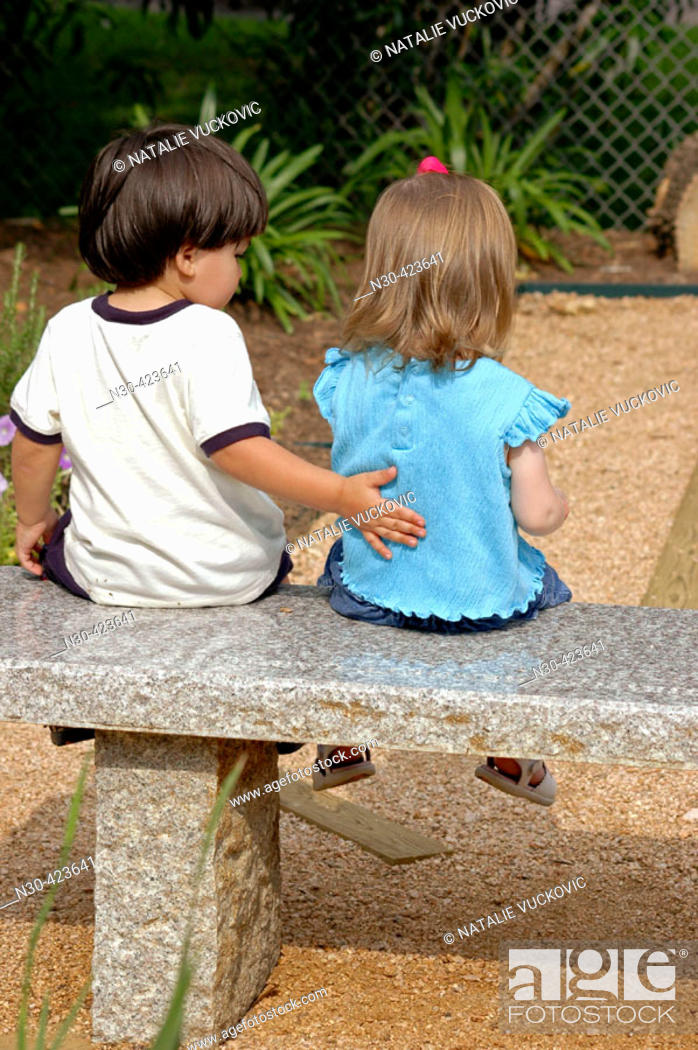 Stock Photo: Toddler boy and girl sitting on park bench.