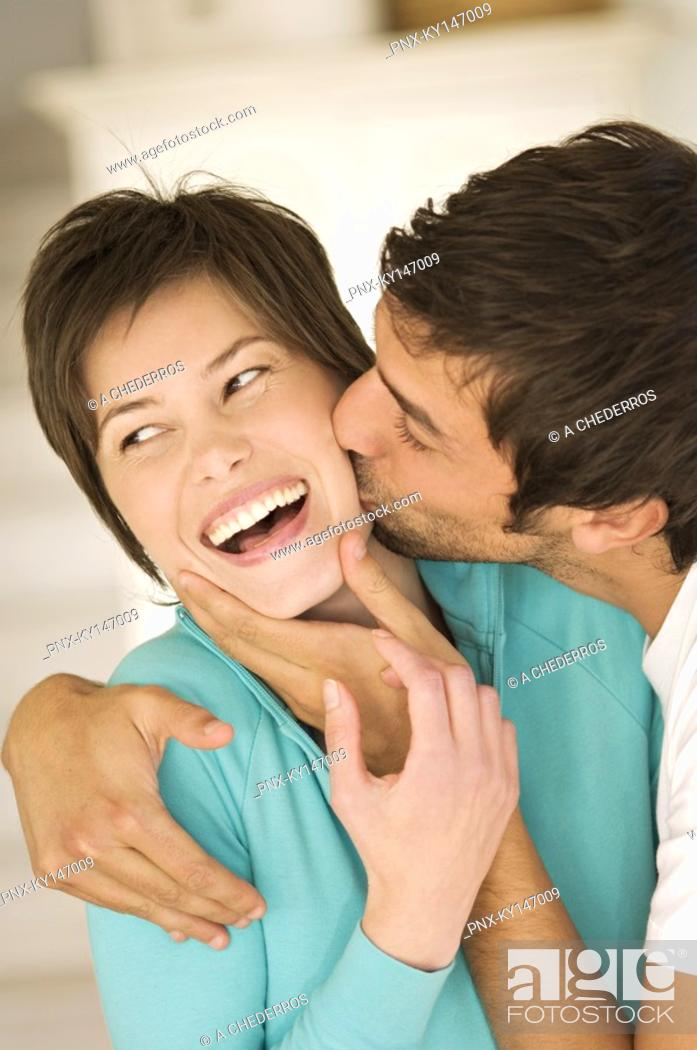 Stock Photo: Portrait of man kissing smiling woman.