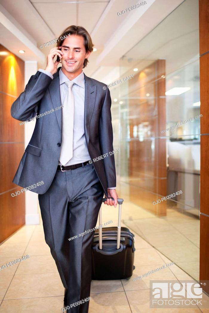 Stock Photo: Businessman talking on cell phone and pulling suitcase.