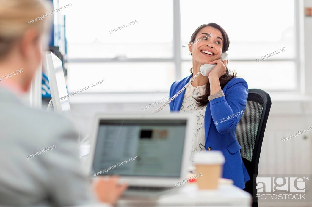 Imagen: Mid adult businesswoman using telephone in office.