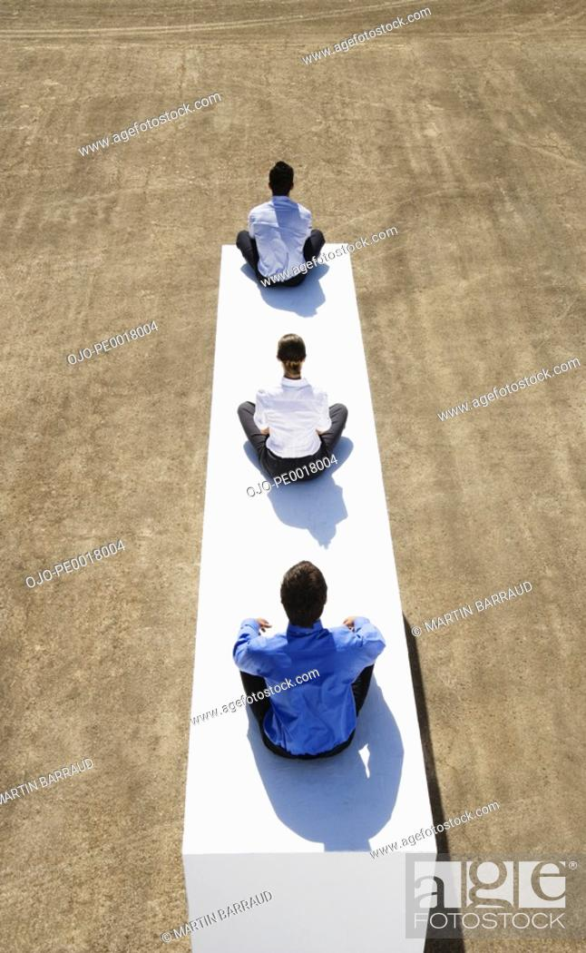 Stock Photo: Three businesspeople sitting cross legged on wall outdoors.