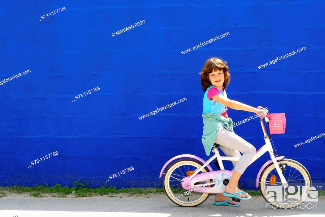 Stock Photo: 7 years old girl on bicycle front a blue wall in Caños de Meca, Cádiz, Andalucia, Spain.