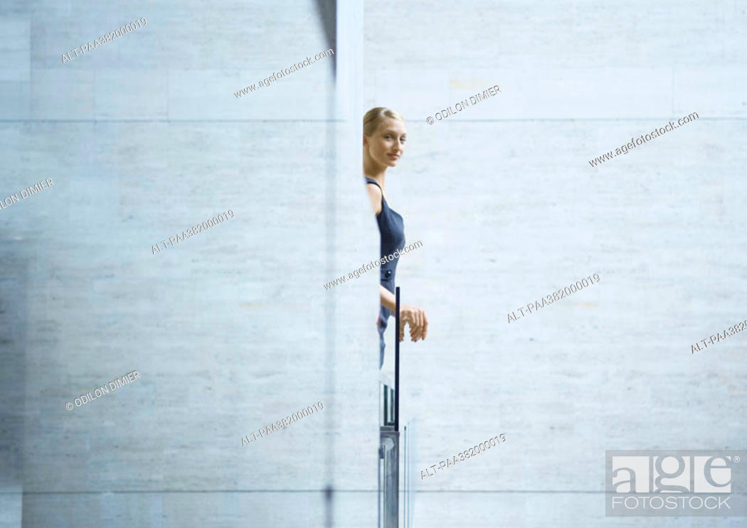 Stock Photo: Woman looking out from behind wall.