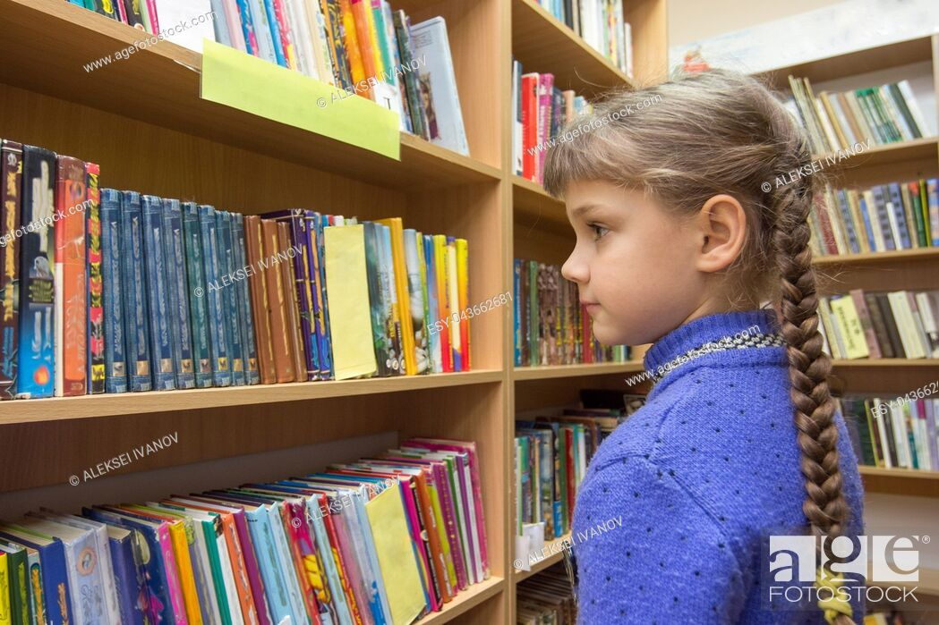 Stock Photo: The girl chooses books in the library.