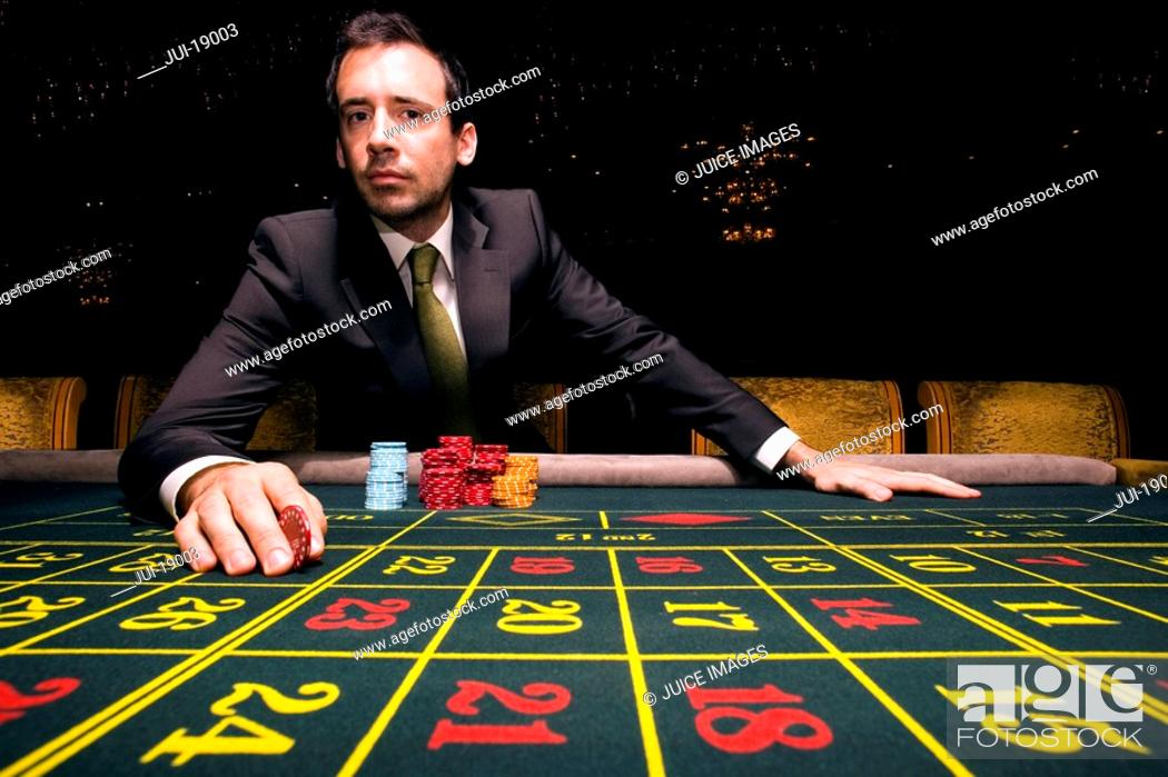 Stock Photo: Man gambling at roulette table, portrait, low angle view.