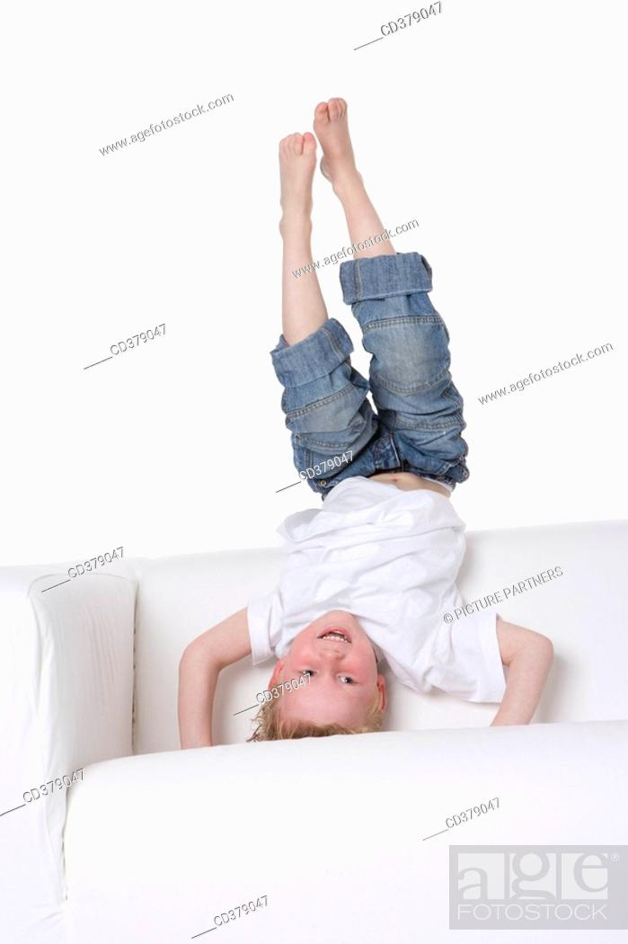 Stock Photo: Boy standing in a headstand on a bench.