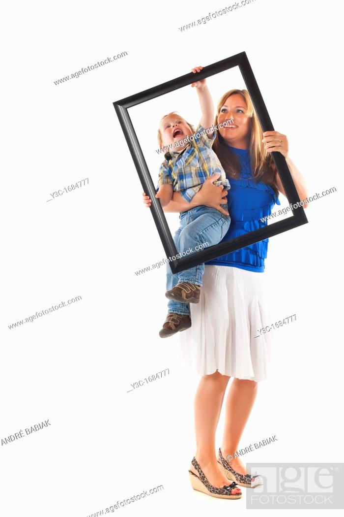 Stock Photo: Young mother with her toddler son trying to prepare for a portrait photograph involving a picture frame.