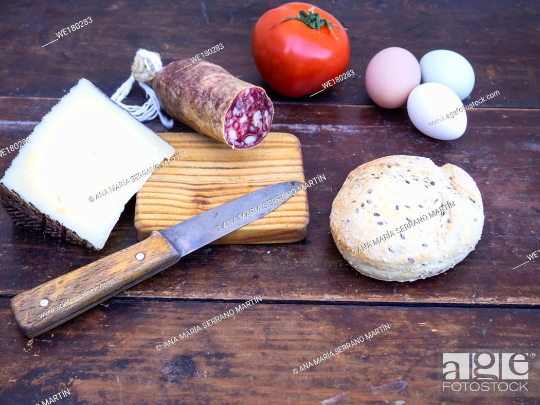 Imagen: An Iberian pork sausage on an old wooden board with an antique knife, a loaf of Spanish rustic seed bread, cheese, one tomato and three multicolor eggs.