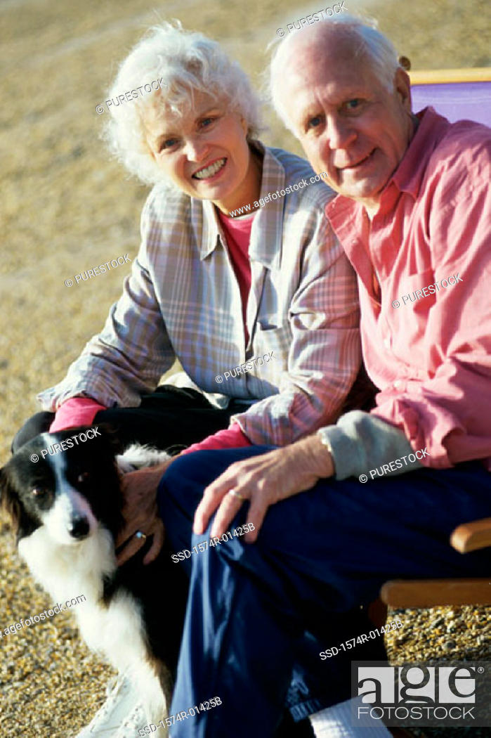 Stock Photo: Portrait of a senior couple sitting with their dog.