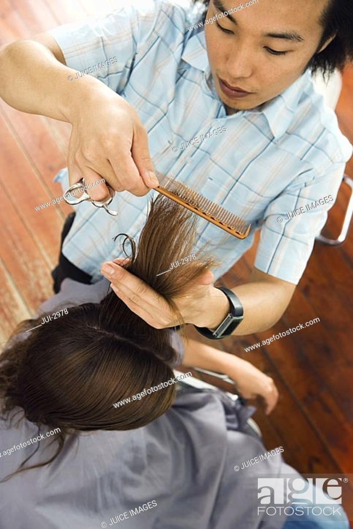 Stock Photo: Young male hairdresser combing woman's hair in salon, close-up, overhead view.
