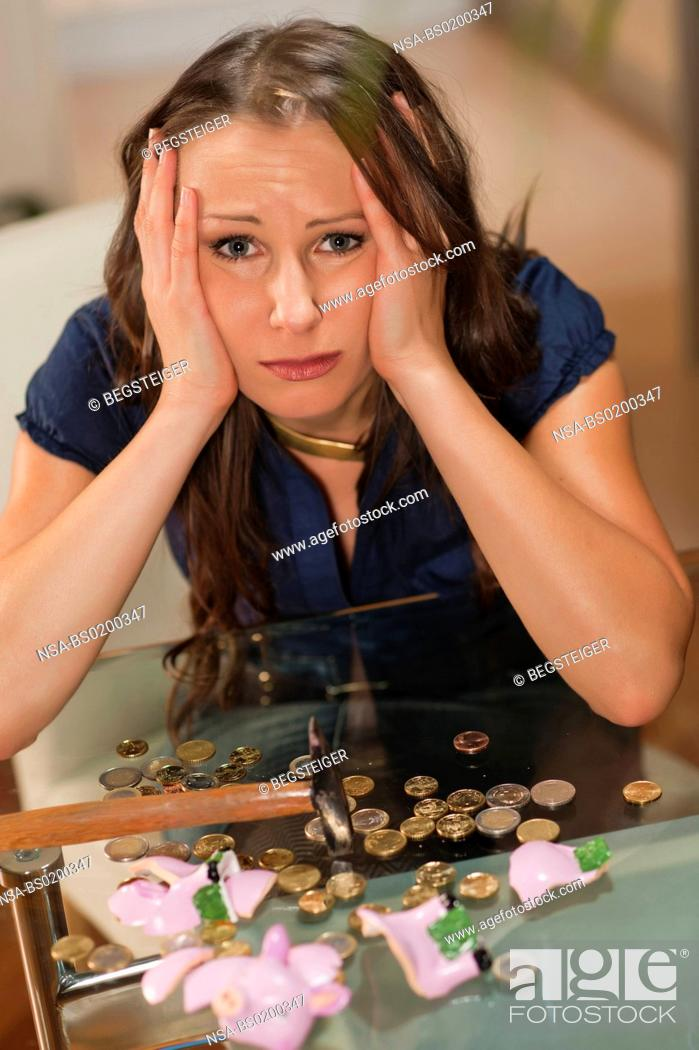Stock Photo: desperated woman with butchered piggy bank.