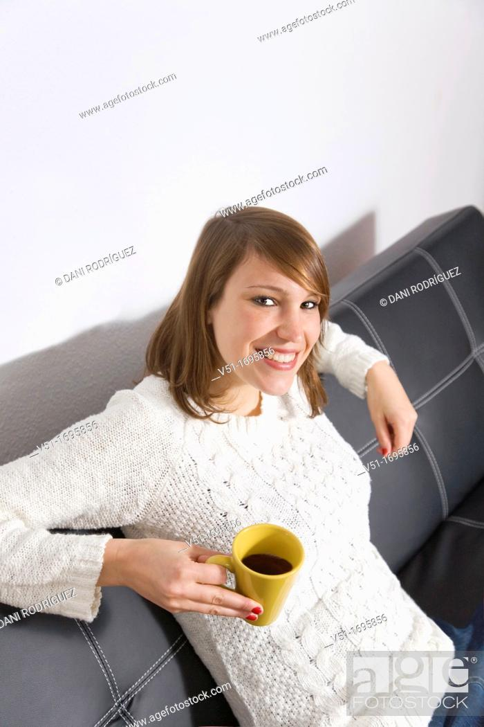 Stock Photo: Pretty woman enjoying a coffe at home on the sofa, smiling at camera.