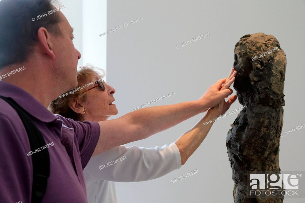 Stock Photo: Woman with visual impairment touching a sculpture at Yorkshire Sculpture Park.