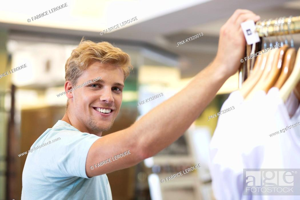 Stock Photo: Portrait of a young man standing in a clothing store.