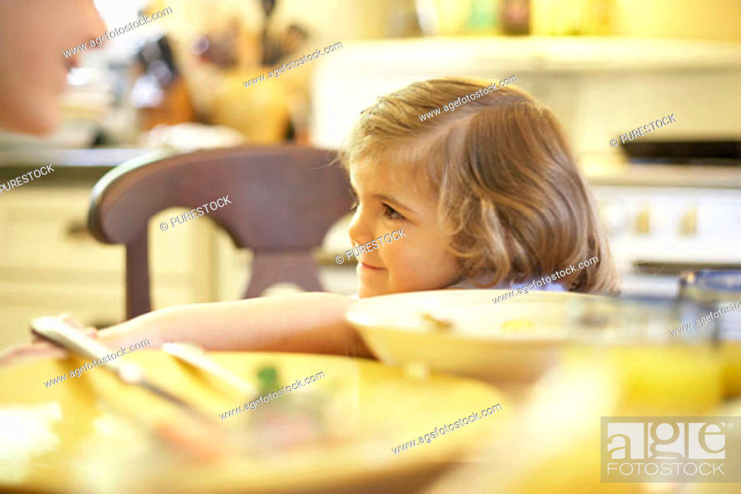 Stock Photo: Girl sitting at a dining table and smiling.