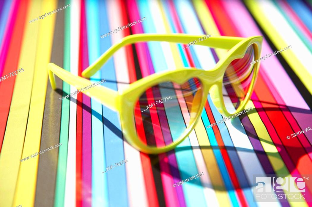 Stock Photo: Heart shaped sunglasses on a multi coloured stripey background.