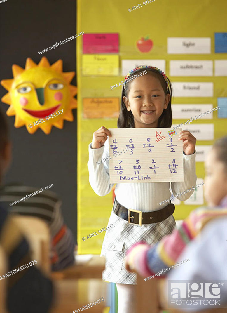 Stock Photo: Young girl in classroom holding up math sheet.