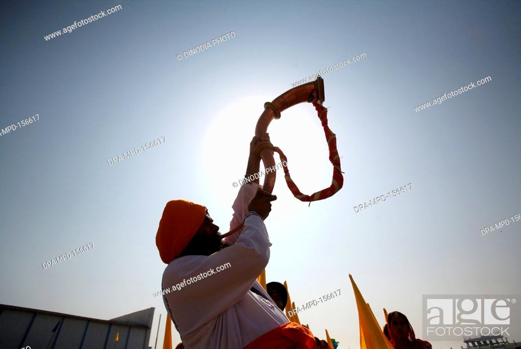 Stock Photo: Sikh devotee blowing tutari trumpet before start of cultural events ; celebrations of 300th year of consecration of perpetual Guru Granth Sahib ; Nanded ;.