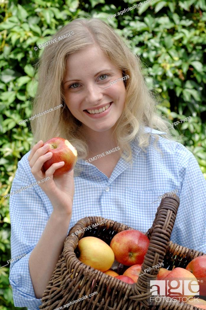Stock Photo: Woman with basket full of apples.