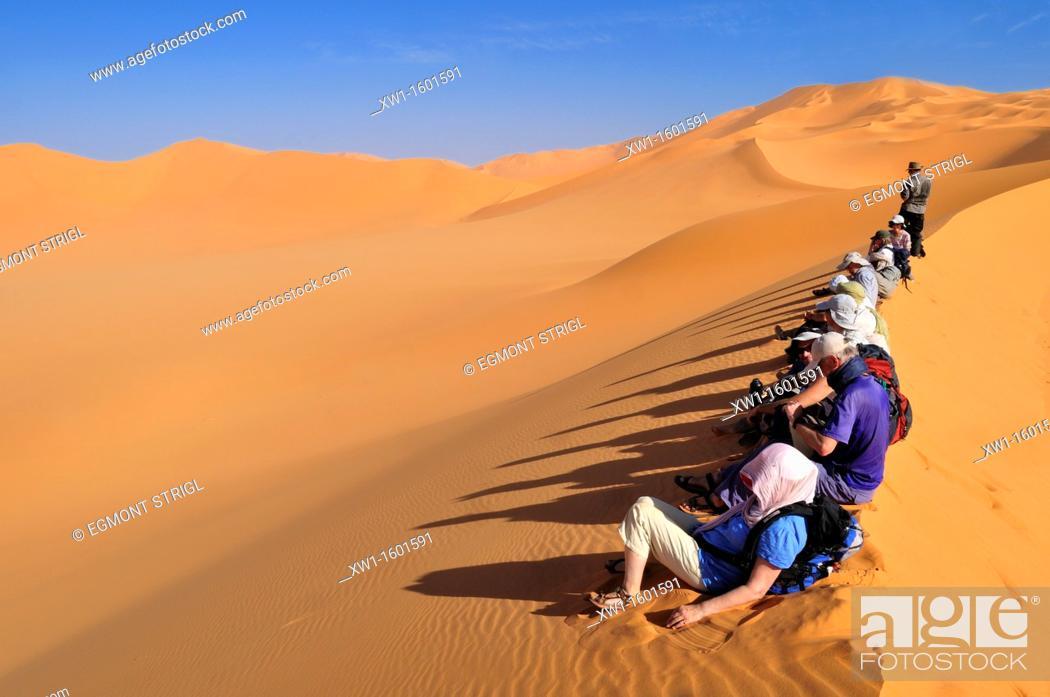 Stock Photo: group of tourists sitting on a sanddune of Erg Mehedjibat, Adrar n' Ahnet, Algeria, Sahara, North Africa.