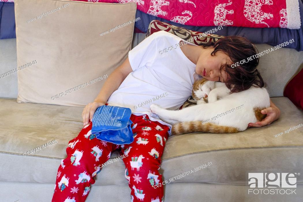 Stock Photo: A boy with injured hand holds an ice pack and snuggles cat for comfort.