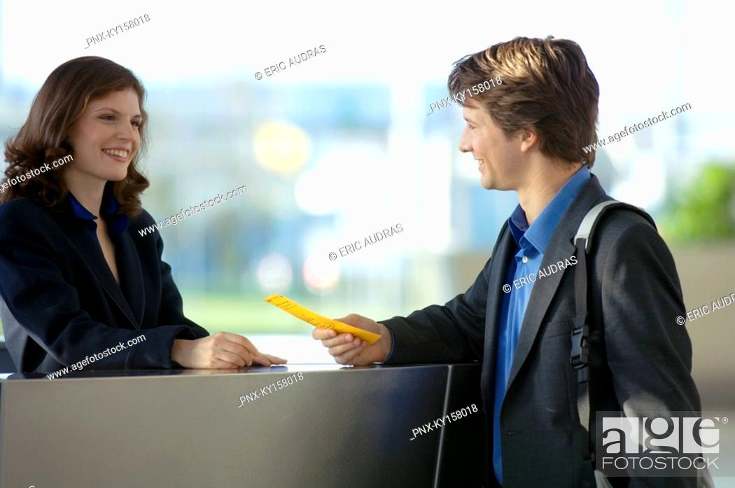 Stock Photo: Businessman holding a bill and talking to a receptionist.