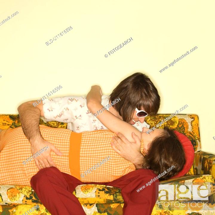 Stock Photo: Couple smiling and embracing on colorful retro sofa.