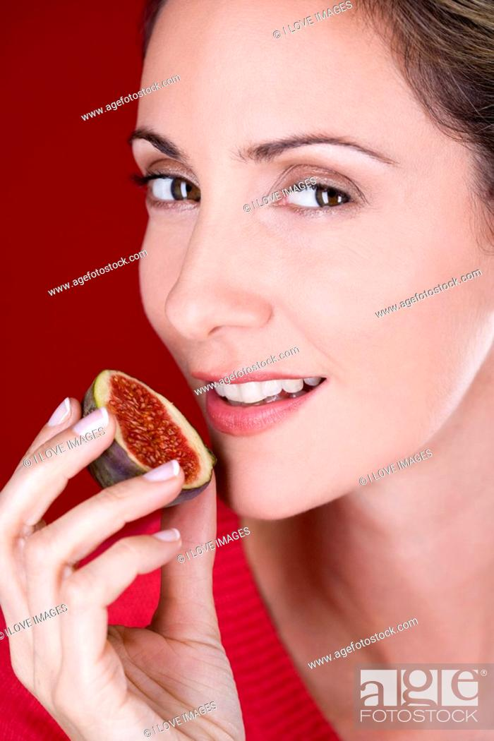 Stock Photo: A mid adult woman eating a fig.