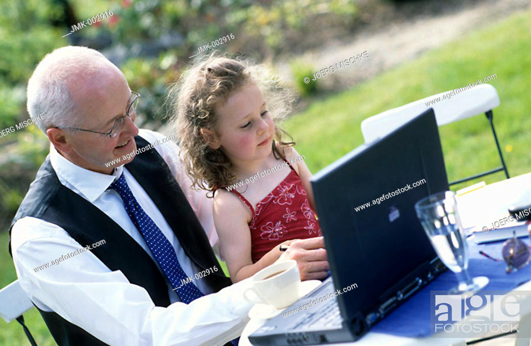 Stock Photo: A senior, businessman, father, grandfather, 45-50 50-55 55-60 years old, sitting at a table in the summerly garden with a little girl, 1-5 5-10 years old.