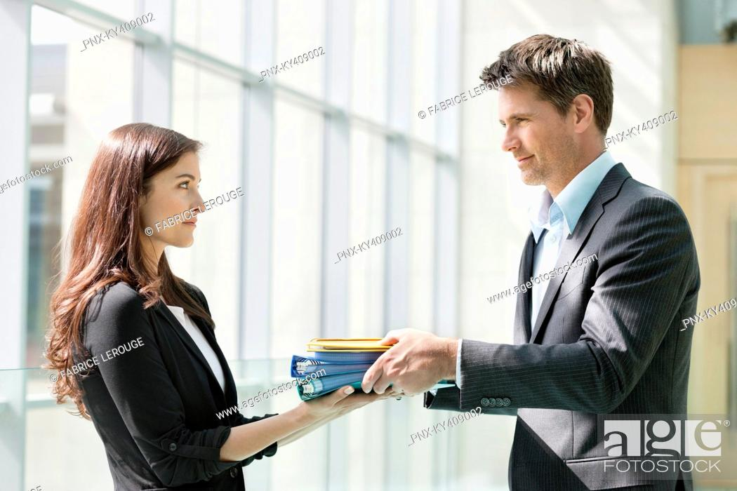 Stock Photo: Businessmen giving files to his female colleague in an office.