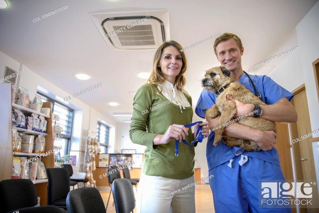 Stock Photo: Veterinarian holding dog in lobby.