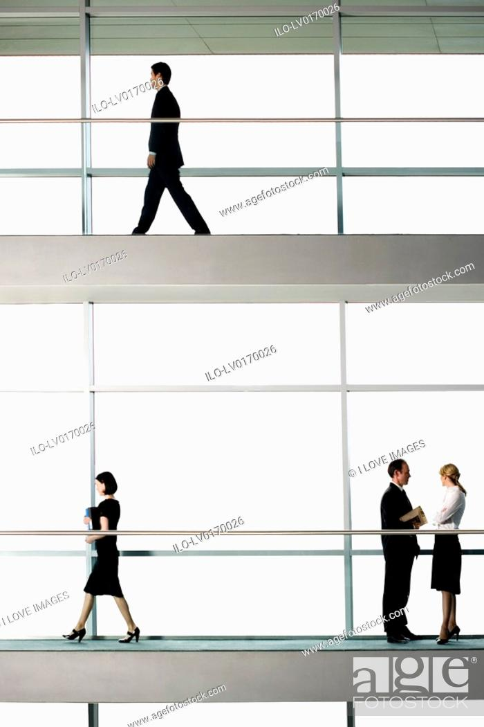 Stock Photo: Office workers walking around modern office building.