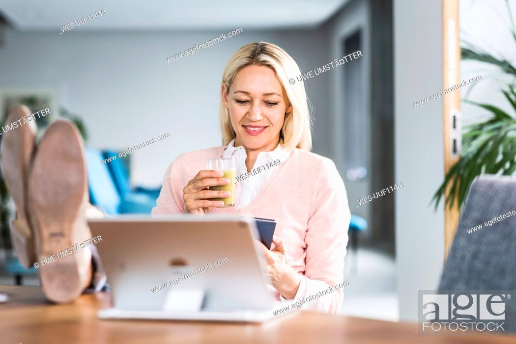 Stock Photo: Businesswoman holding smoothie and using cell phone in office.