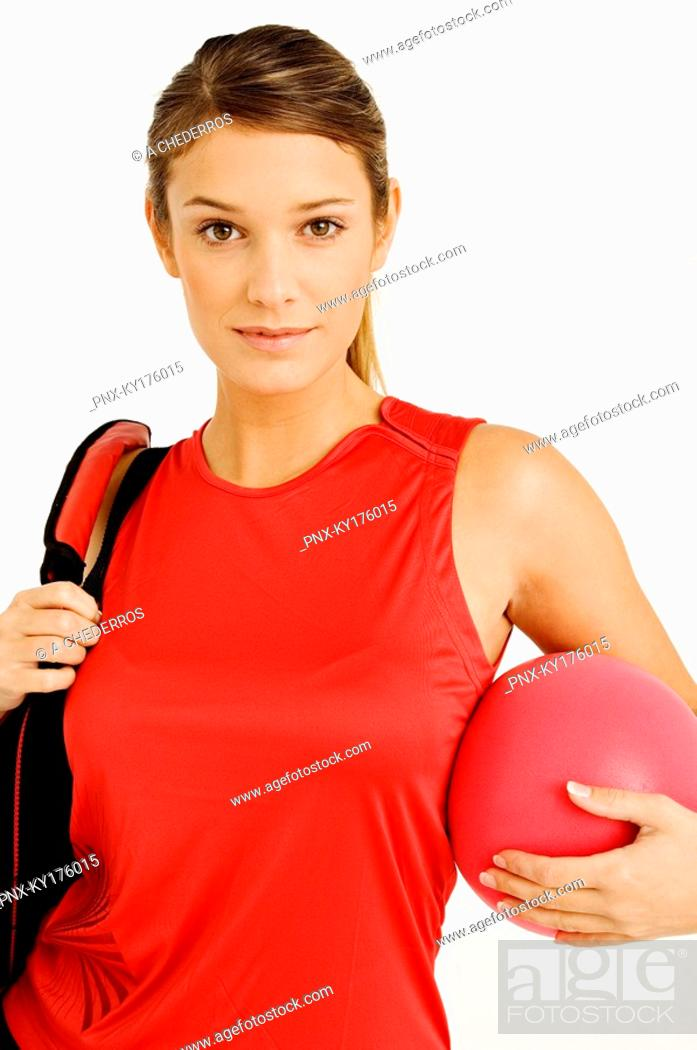 Stock Photo: Portrait of a young woman carrying a gym bag and a ball.