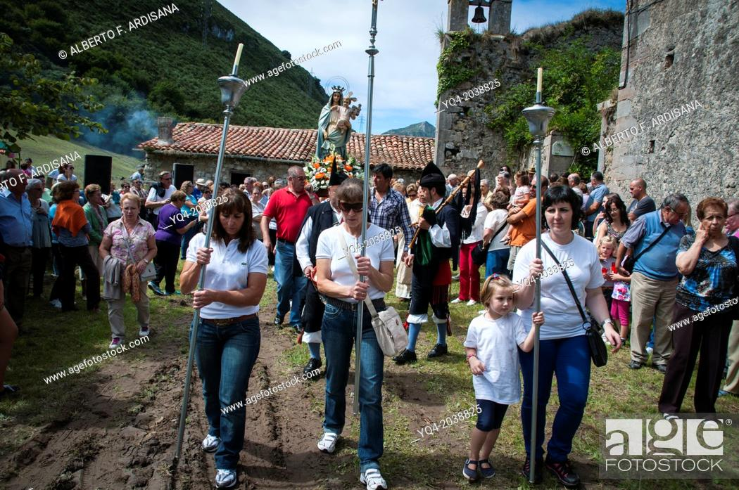 Stock Photo: Three women in jeans, lead the modest procession of Loreto. Llanes, Asturias, Spain.
