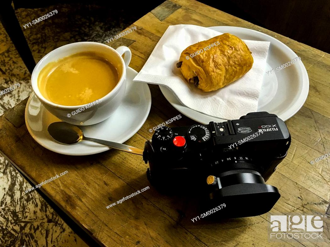 Imagen: Berlin, Germany. Cup of Coffee with Chocolate Croissant and digital compact camera on a coffee-place's table.