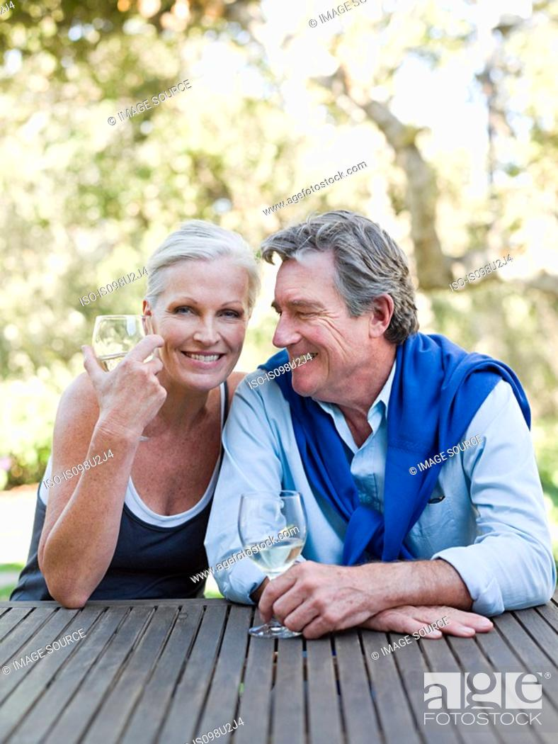 Stock Photo: Mature couple outdoors with wine.