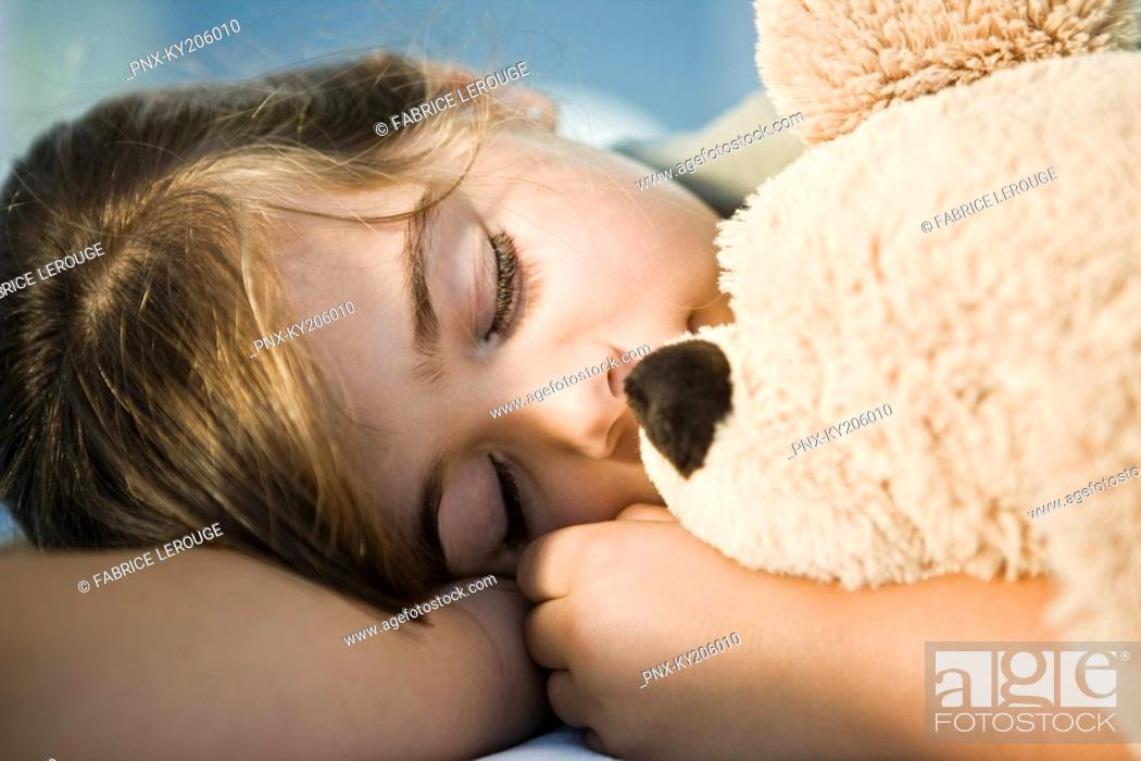 Stock Photo: Close-up of a girl sleeping with a teddy bear.
